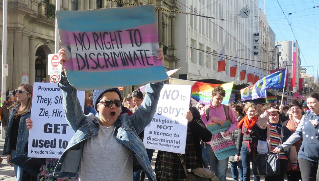"""A woman at a rally holds a sign saying """"No right to discriminate."""""""