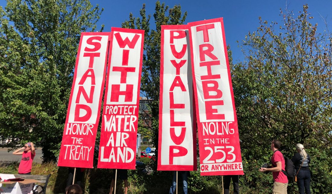 """Four vertical banners. The large words are STAND WITH PUYALLUP TRIBE. Smaller words include """"Honor the treaty,"""" """"Protect water and land,"""" and """"No LNG in the 253 or anywhere."""""""