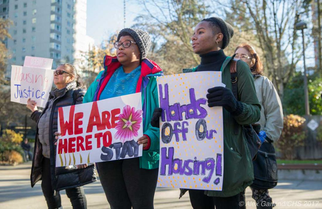 """Two women hold signs. One says """"We are here to stay,"""" and the other """"Hands off our housing!"""" They are outside, with trees, blue sky, and a tall building in the background."""