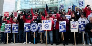 A large multiracial group of men and women with UAW picket signs.